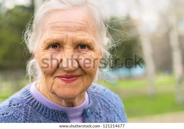 Porträt einer lächelnden älteren Frau. Ein Foto auf Naturhintergrund