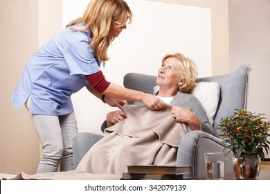 Portrait of smiling elderly woman sitting at home in living room and accepts caregiver assistance.