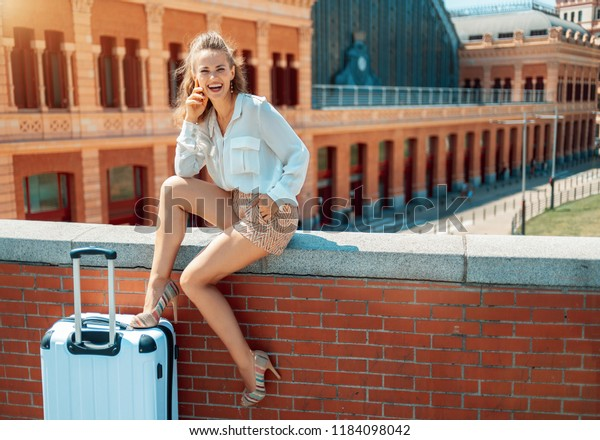Portrait of smiling elegant tourist woman with trolley bag in the front of Puerta de Atocha while sitting on parapet