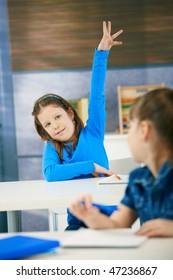 Portrait of smiling elementary age schoolgirl raising hand in class.