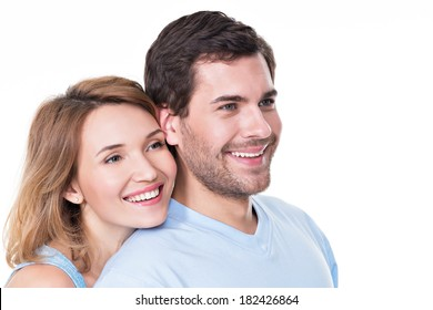 Portrait of smiling embracing couple in casual looking  sideways -  isolated on white background.