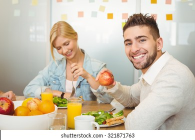 Portrait of smiling employee with female colleague having breakfast in creative office