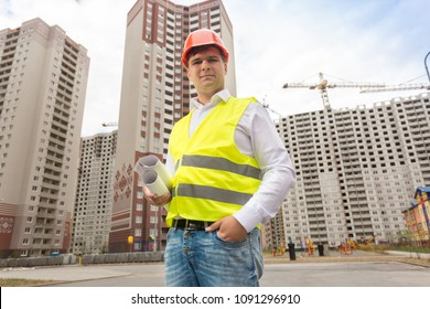 Portrait of smiling engineer in hardhat standing with blueprints against building under construction