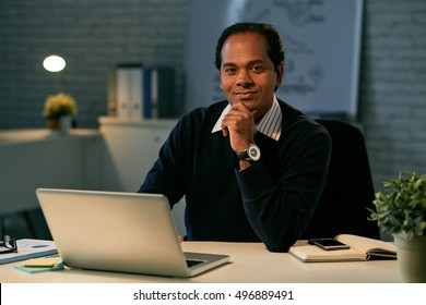 Portrait of smiling entrepreneur sitting at his workplace