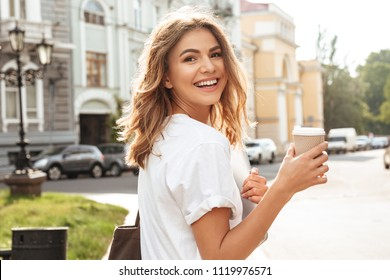 Portrait of smiling european woman strolling through city street with silver laptop and takeaway coffee in hands
