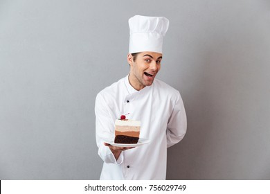 Portrait of a smiling excited male chef dressed in uniform holding plate with piece of cake and looking at camera isolated over gray background