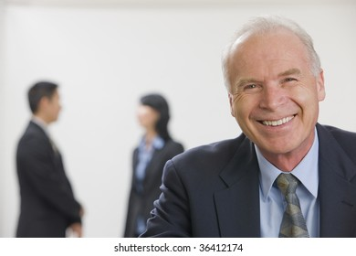 Portrait of smiling executive with co-workers out of focus in the background.