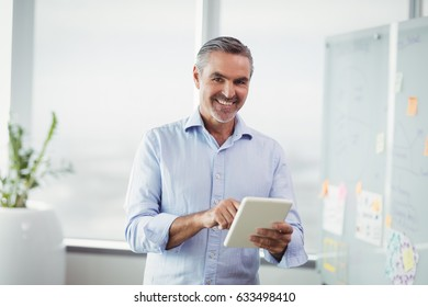 Portrait of smiling executive using digital tablet in office