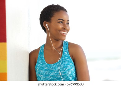 Portrait of smiling exercise woman listening to music with earphones outside
