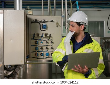 Portrait of smiling factory engineer in the beverage factory production line. Factory worker controlling production.