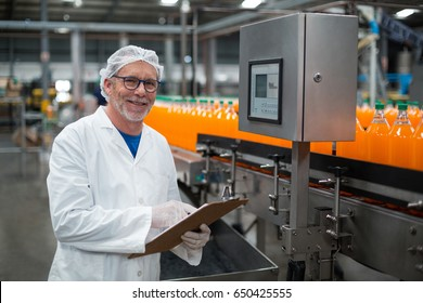 Portrait of smiling factory engineer maintaining record on clipboard in drinks production plant