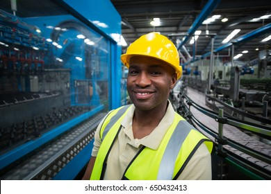 Portrait of smiling factory worker at drinks production plant