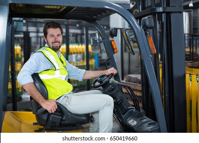 Portrait of smiling factory worker driving forklift in factory