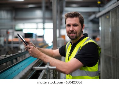 Portrait of smiling factory worker using a digital tablet in factory