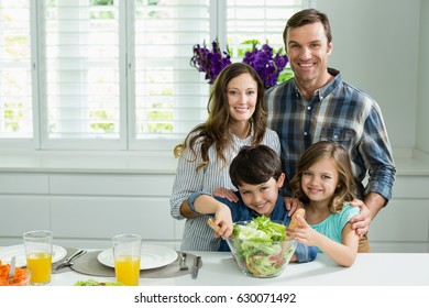 Portrait of smiling family preparing bowl of salad in kitchen at home