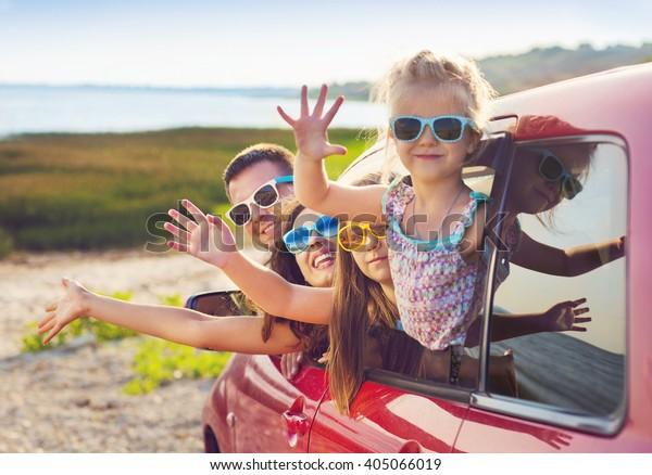 Portret van een lachend gezin met twee kinderen op het strand in de auto. Vakantie en reisconcept