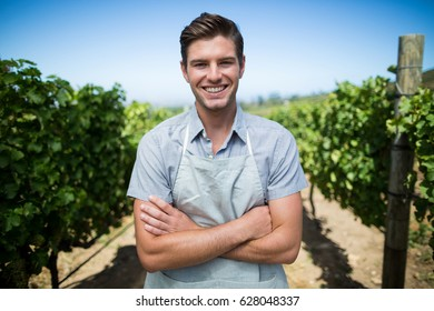 Portrait of smiling farmer with arms crossed standing at vineyard