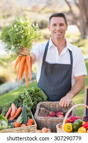 Portrait of a smiling farmer handing a bunch of carrots