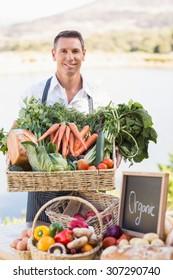 Portrait of a smiling farmer holding a basket of vegetables