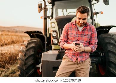 Porträt von lächelnden Bauern mit Smartphone und Traktor bei der Ernte. Moderne Landwirtschaft mit Technologie- und Maschinenkonzept