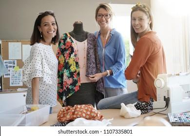 Portrait of smiling fashion designers in workshop