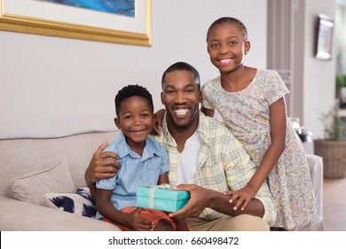 Portrait of smiling father and children holding gift box on sofa at home