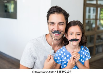 Portrait of smiling father and daughter with artificial mustache at home