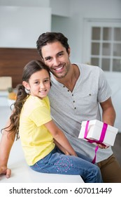 Portrait of smiling father and daughter with gift box at home