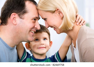 A portrait of a smiling father, a mother and a little son