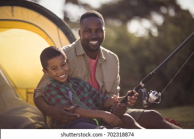 Portrait of smiling father and son fishing together in park