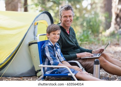 Portrait of smiling father and son with laptop in forest