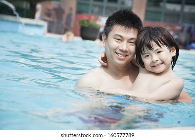 Portrait of smiling father and son in pool on vacation