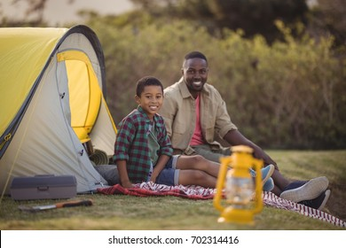 Portrait of smiling father and son sitting together in park