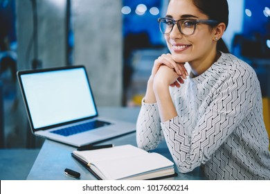 Portrait of smiling female administrator in eyewear satisfied with occupation organizing work in office using netbook ,positive manager looking at camera sitting near laptop with mock up screen