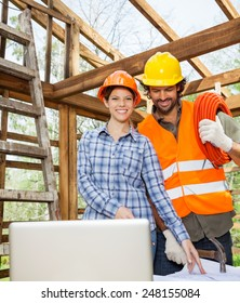 Portrait of smiling female architect working with construction worker at site