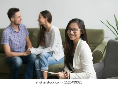 Portrait of smiling female asian counselor with happy couple at background, professional chinese psychologist looking at camera, marriage counseling therapy and family problems solution concept