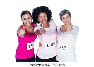 Portrait of smiling female athletes with thumbs up while standing against white background