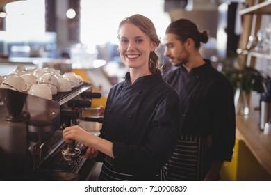 Portrait of smiling female barista using espresso maker against waiter at coffee shop