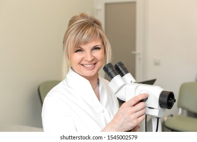 Portrait of a smiling female blond doctor gynecologist near colposcope. Examination by a gynecologist. Female health concept.
