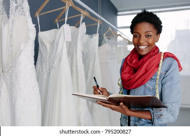 Portrait of smiling female bridal store owner with a diary. Wedding dress designer working in her boutique.