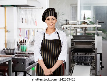 Portrait of smiling female chef standing in commercial kitchen