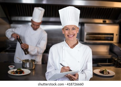 Portrait of smiling female chef writing on clipboard in commercial kitchen