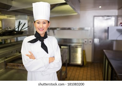 Portrait of a smiling female cook standing in the kitchen