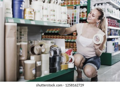 portrait of smiling female customer 20s picking adhesive tape in housewares department