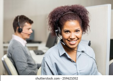 Portrait of smiling female customer service representative with male colleague in background at office