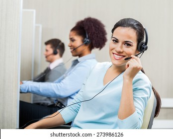 Portrait of smiling female customer service representative wearing headset with colleagues working in background at office