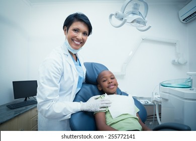 Portrait of smiling female dentist examining boys teeth in the dentists chair