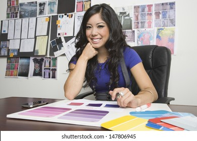 Portrait of a smiling female fashion designer working at desk