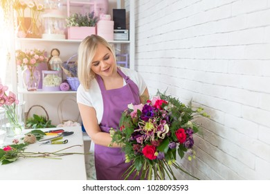 Portrait of smiling female florist with full of flower plants in shop. Woman creates a flower arrangement or composition for the Spring Festival or another holiday