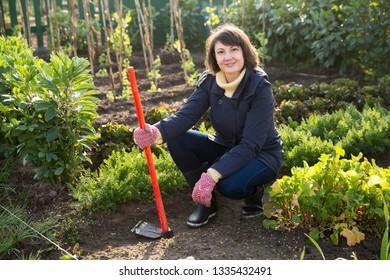 Portrait of smiling female gardener working with hoe, hoeing vegetable garden soil